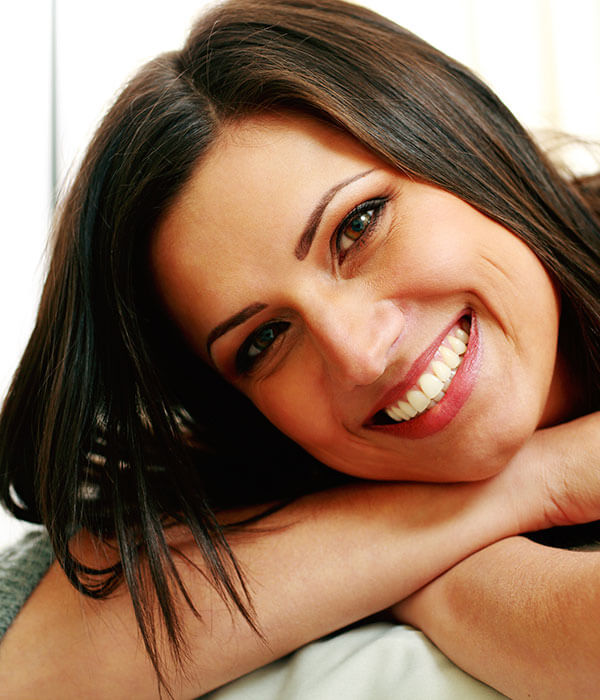 A woman with a beautiful smile lying on her hands while smiling