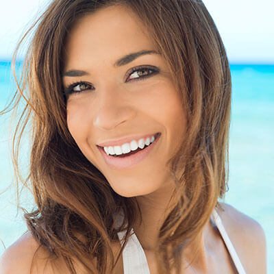 A young woman smiling on the beach with beautiful teeth