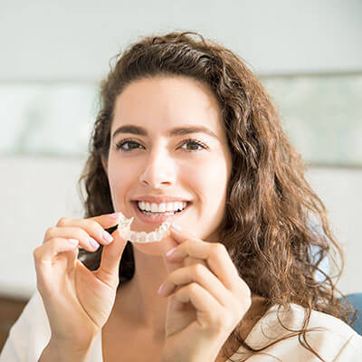 A young woman putting on her mouthguard