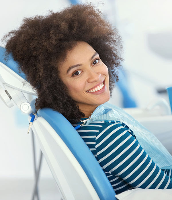 A young woman smiling from a dental chair