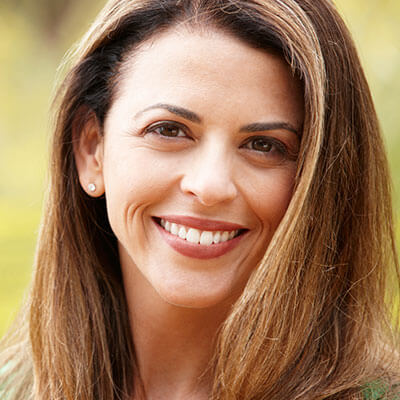 A mature woman smiling in a park